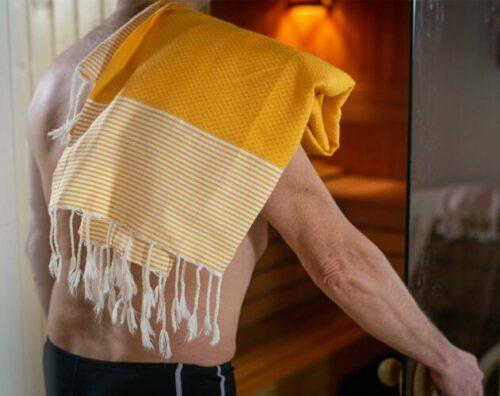 Heading into a sauna with a hammam towel