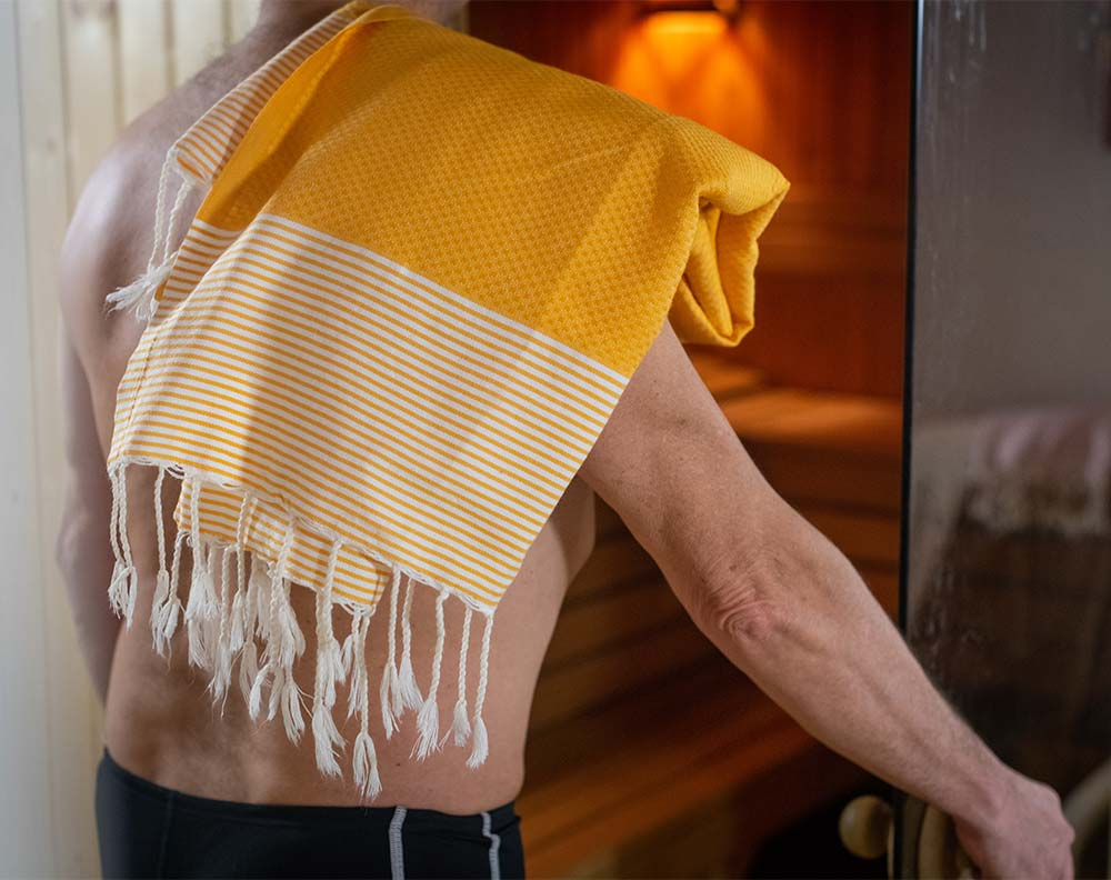 Heading into a sauna with a hammam towel